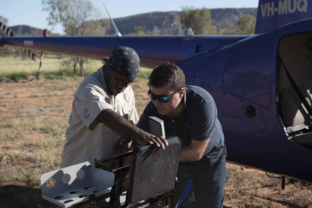 Jigalong ranger, Errol Samson, learning from trainer Julian about how to install the frame into the helicopter