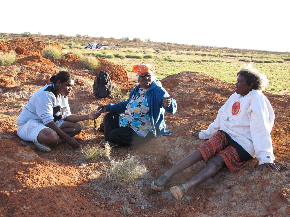 May tells a story to Morika Biljabu at Wilunaninja Rockhole while Jakayu listens;