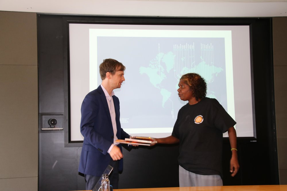 Women's leadership participant, Sandra Nixon, hands a KJ thank you gift to James Sippe from Herbert Smith Freehills during their training session on company law.