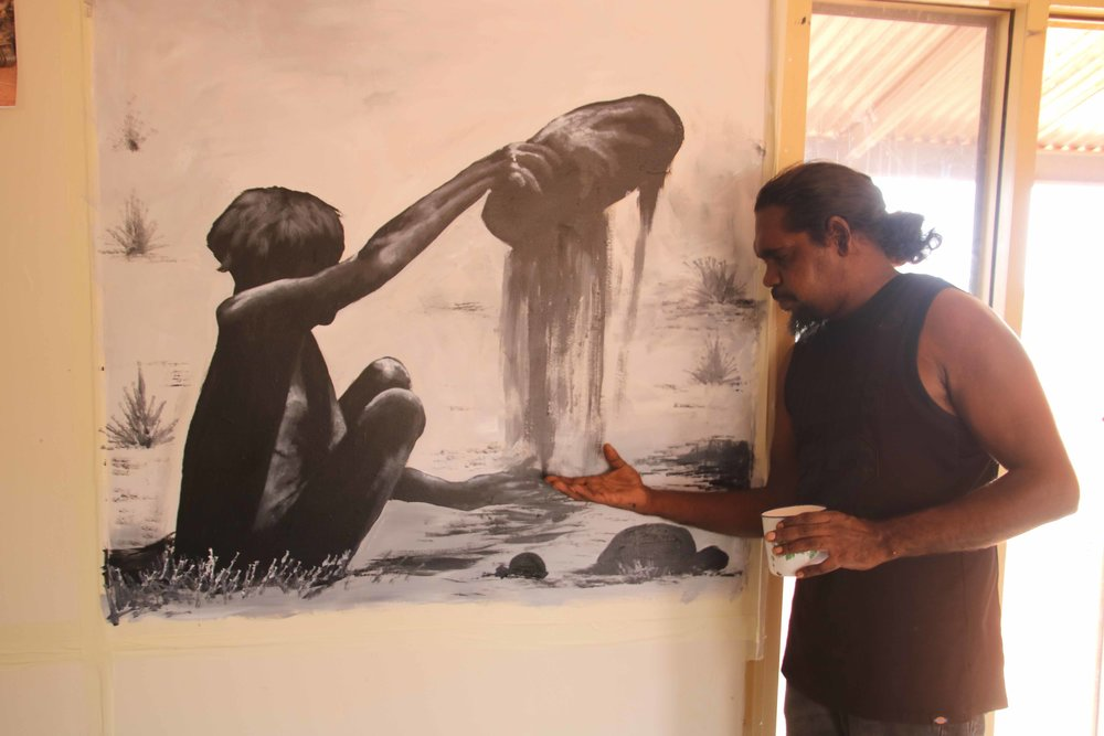 Ranger and artist Owen Biljabu proud of his painting depicting a pujiman (bushman) lady preparing seed for grinding