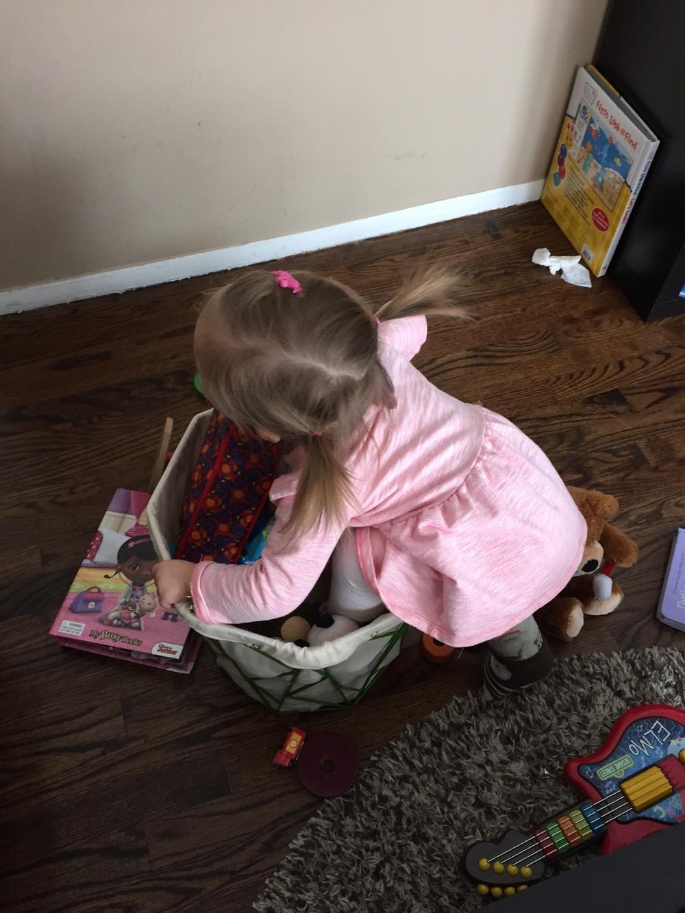 Toddler climbing in toy bin