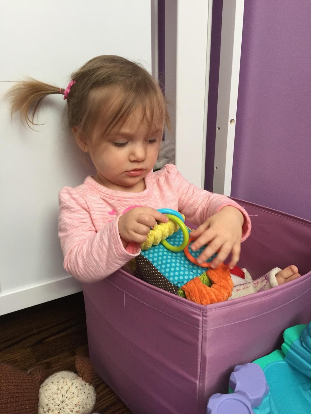 Toddler in toy bin