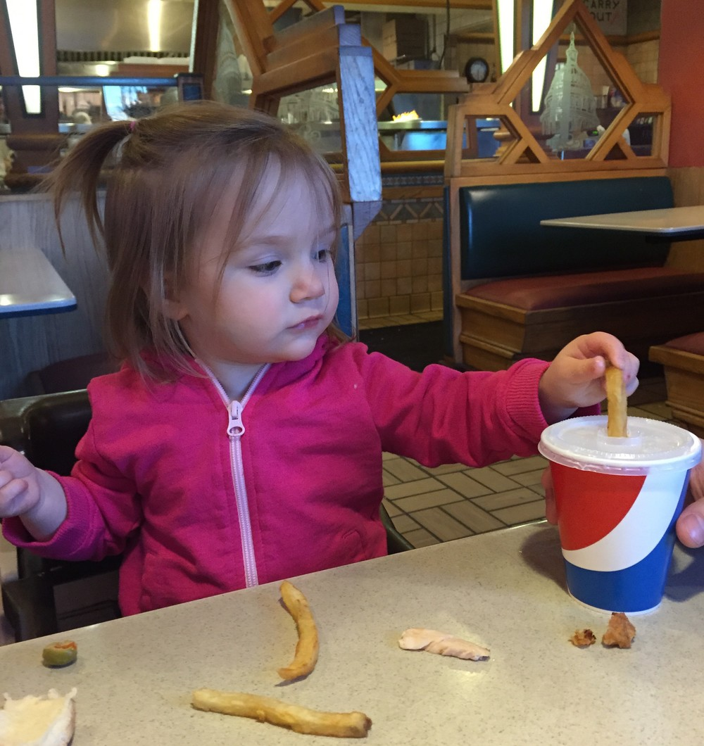 Toddler using fries as straws