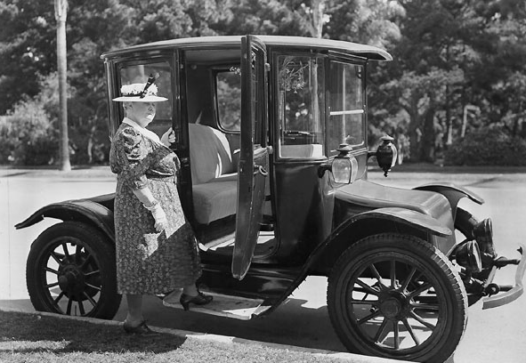 A lady steps into a Detroit Electric automobile
