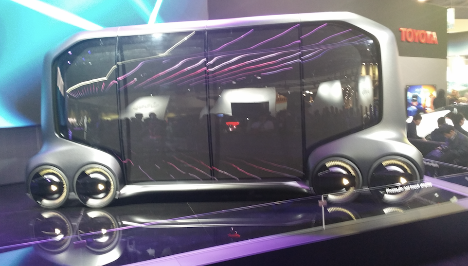 Toyota autonomous bus with advertising billboards on side panels.