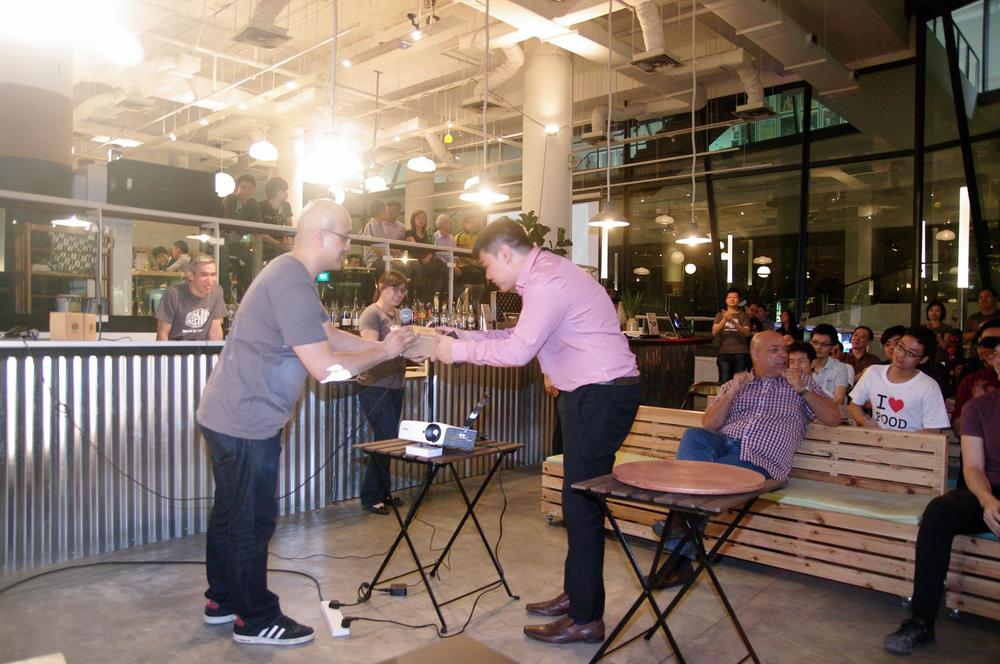 Here's OMGeek's Managing Editor Joel Koh accepting a prize for answering the correctly at a quiz type activity. We swear it wasn't rigged, Joel's just fast at raising his hand! [Ed: For the record, it was a simple question, and I got a mug.]