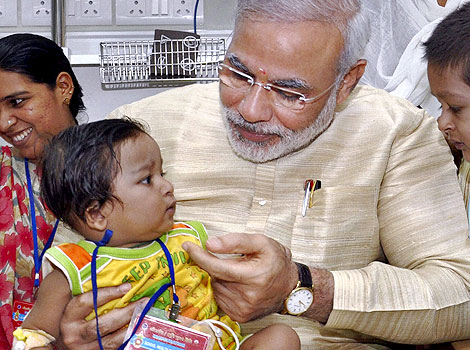 PM Modi, HOLDING A CHILD. PHOTO CREDIT: grems.in