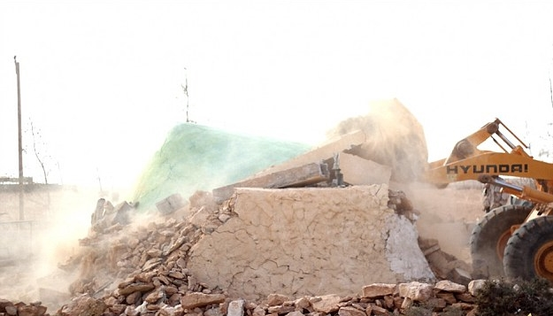 ISLAM FANATICS ULTIMATING THE SHRINES' DESTRUCTION WITH A DIGGER. PHOTO CREDIT: THE GUARDIAN