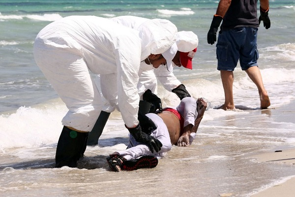 Collecting the body of another refugee washed ashore.