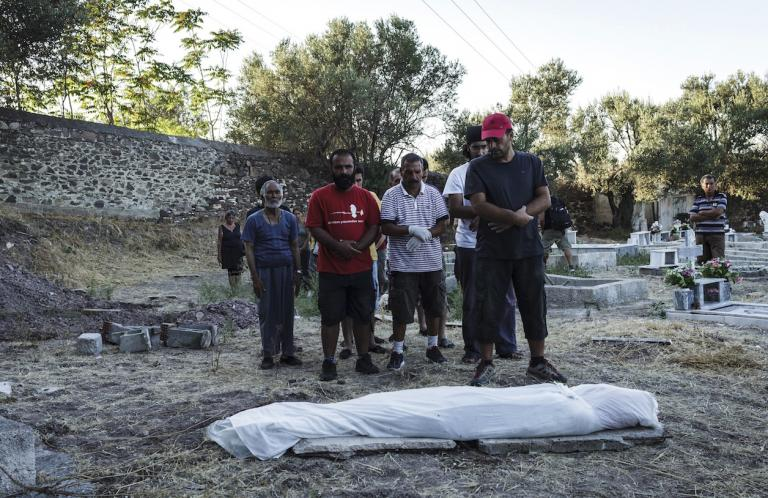 Migrants pray over the dead body of an unidentified refugee from Syria found by the Greek Coast Guard.