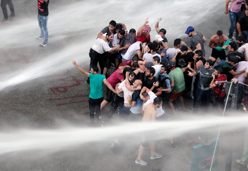 Riot police officers spray protesters with water in Beirut on the second day of protests. Photo credit: Bilal Hussein/AP