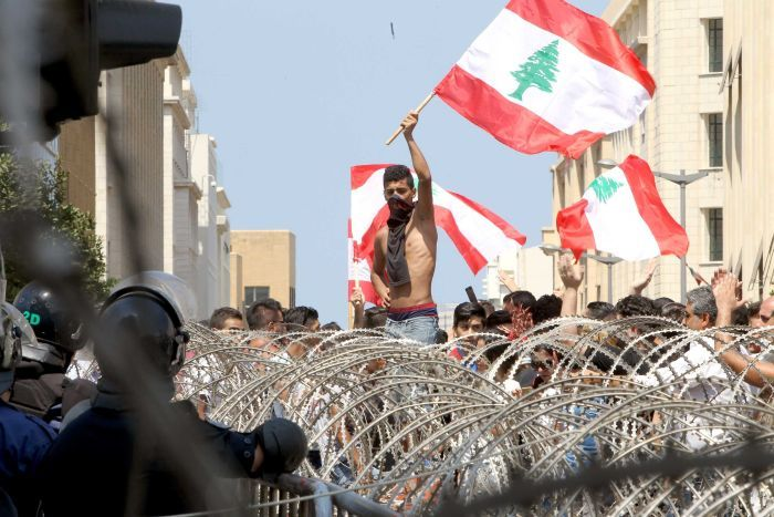Lebanese protesters wave the national flag in front of a barbed wire fence during a demonstration in Beirut. Photo credit: Anwar Amro/AFP
