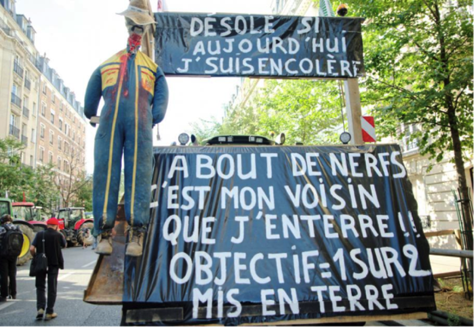 """""""Sorry if I am angry today. Frazzled, it is my neighbor whom I'm burying!! Objective = 1 out of 2 placed underground,"""" the sign of a protesting farmer in Place de la Nation in Paris says. Photo credit: Timothée Cognard/AFP"""