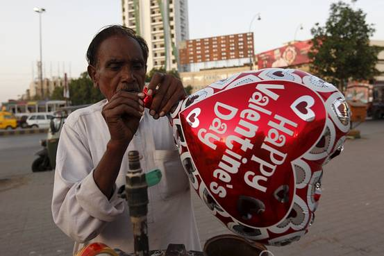 A vendor inflates a heart-shaped balloon in the Pakistani city of Karachi, on Feb. 10, 2016. Credit: Akhtar Soomro/Reuters