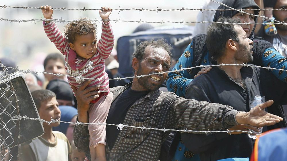 A Syrian refugee carries his child as he waits behind border fences to cross into Turkey. Cover credit:  WordPress