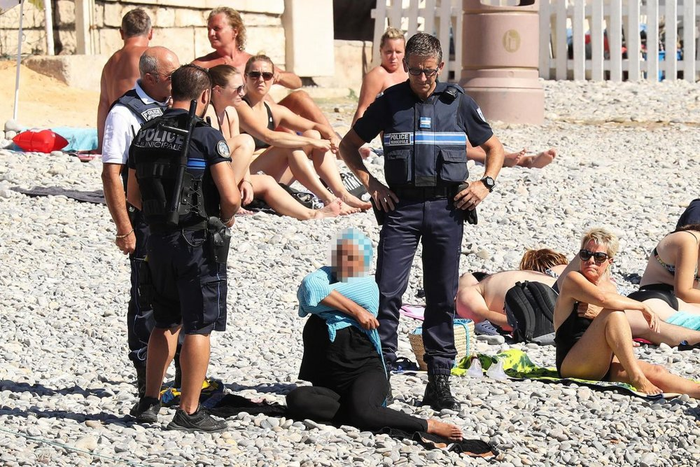 Woman being undressed by police in public in Cannes. Credit: The Independent