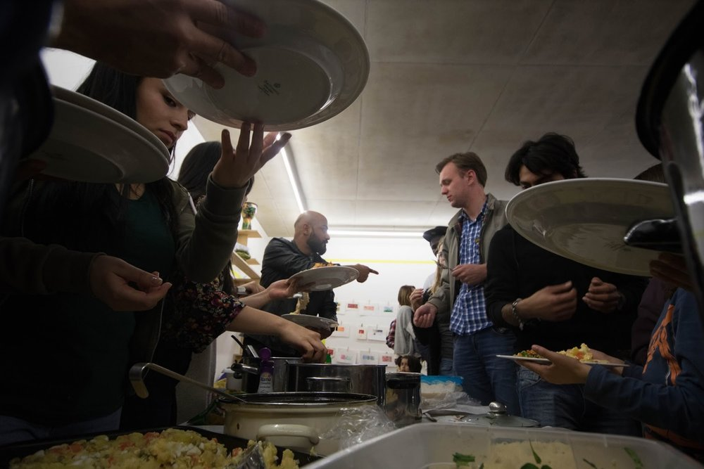 Students and refugees gather to enjoy food made by the welt_raum group. Credit: Claudia Greco