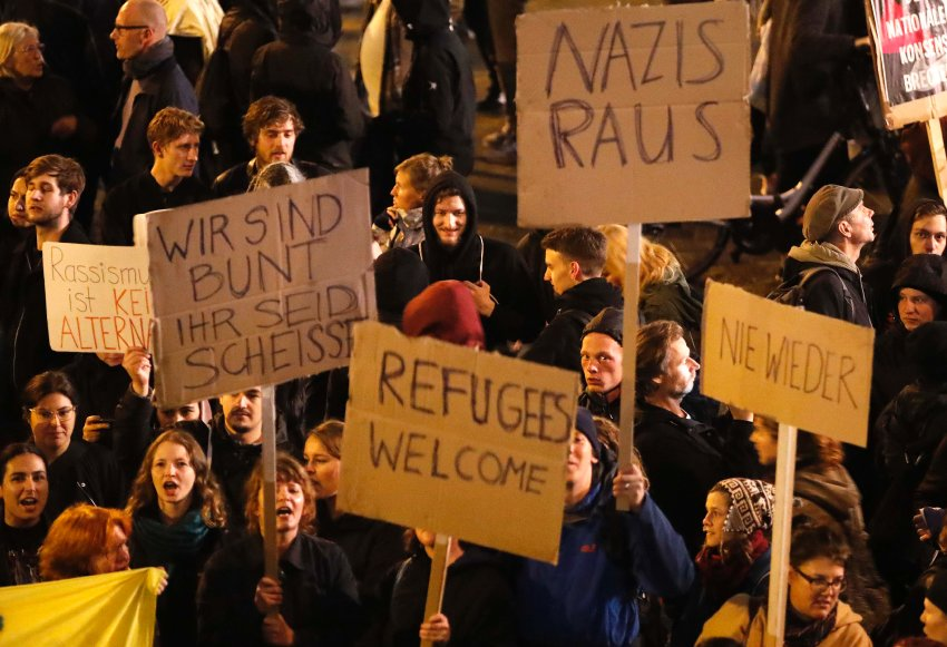 "People are protesting outside of the building in which the AfD is celebrating their election results in Berlin. One of the protesters' sign reads ""Racism is No Alternative"", a word-play on the party name."