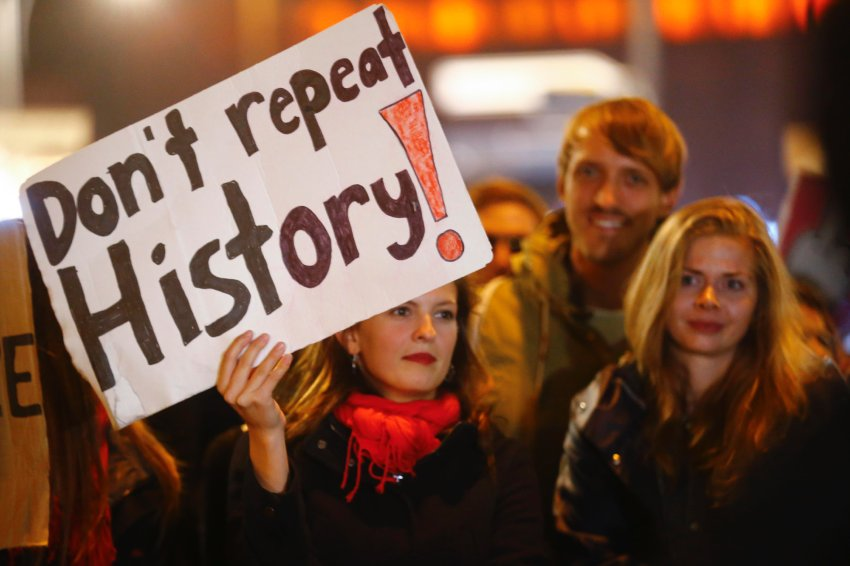 "A woman at one of the protests holds up a sign with the words ""Don't repeat history""."