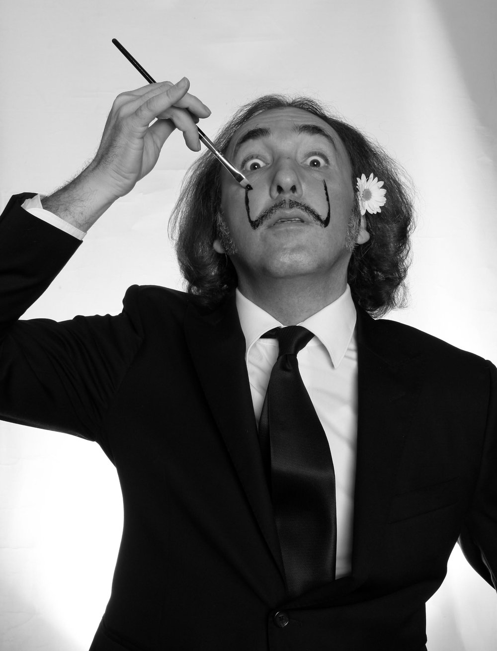 """Do it yourself Dali"" (2012) is a black and white photo of conceptual artist Genco Gulan in which he is painting himself to become the late famous surrealist Spanish draftsman Salvador Dali. Image source:    Wikimedia Commons"