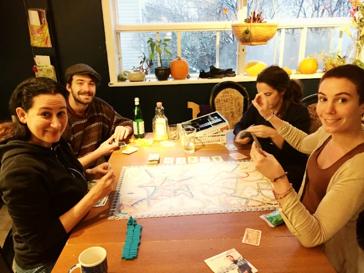 Marie (right) and Aubert (left with the hat) give these ukulele road trips their fair share of interesting facts  in the podcast  ! Here pictured with a couple of  coloc'  and busy with a (board game) road trip of their own.
