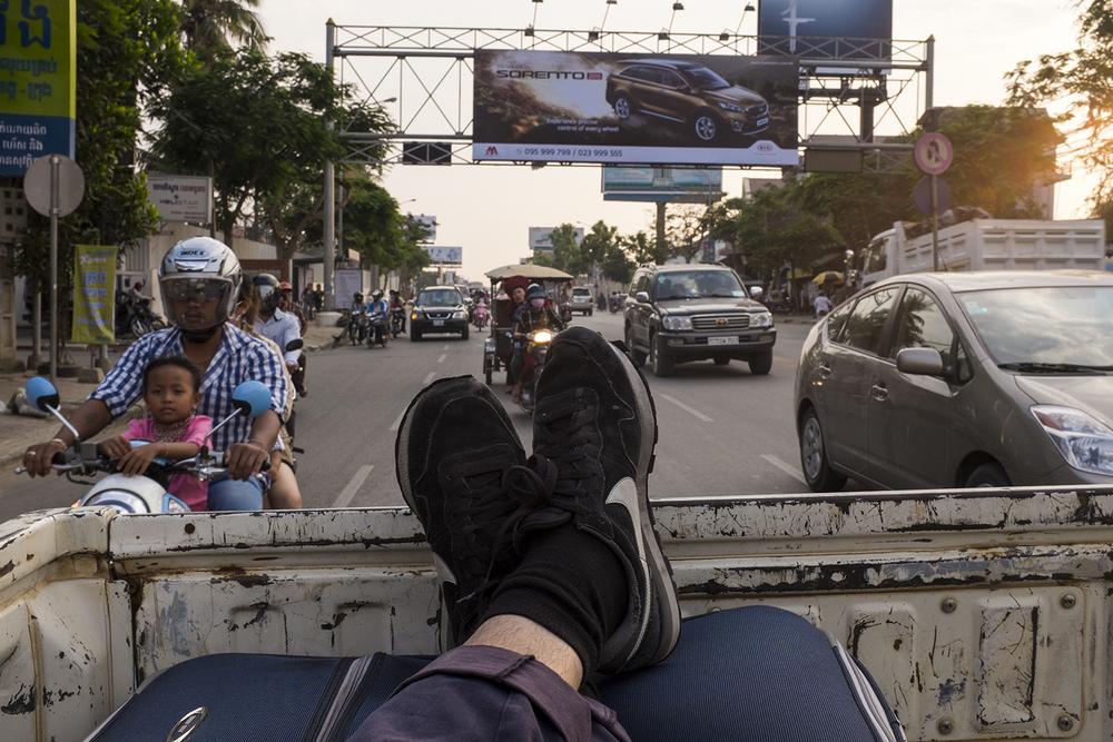 Backseat of a ute, speeding through Cambodian traffic.