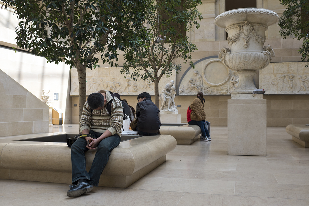 A man sleeping in the Louvre.