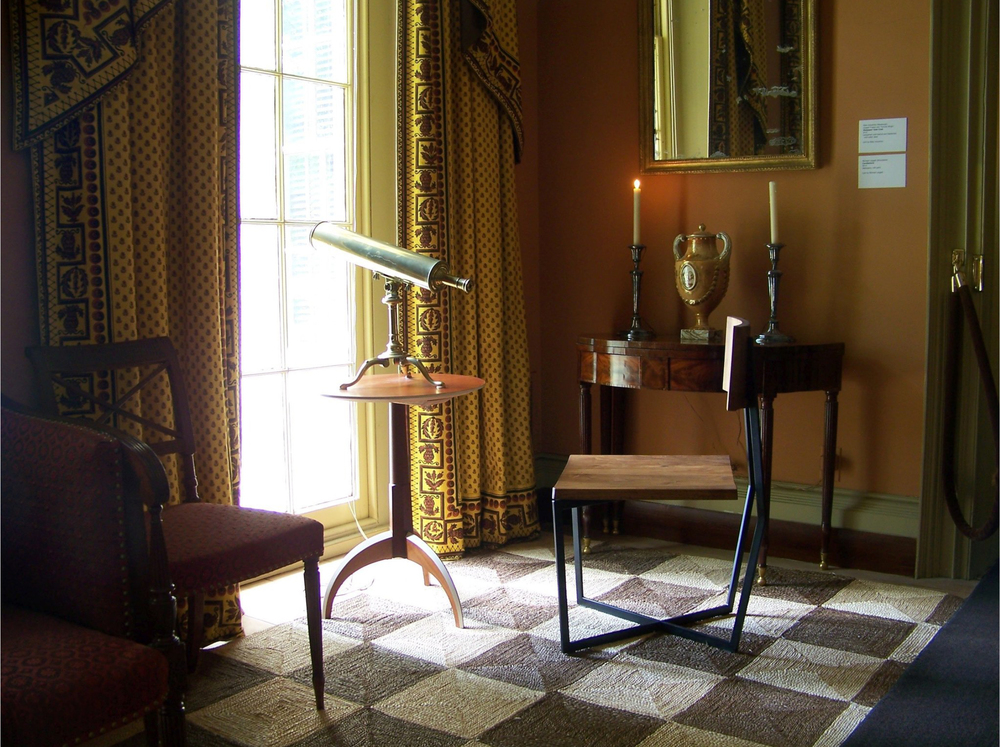 A circa 1800 candlestand reimagined by Michael Leggett is joined by a prototype for a side chair by Atlas Industries that has a walnut seat cantilevered over an X-shaped steel base. CreditBoscobel House & Gardens