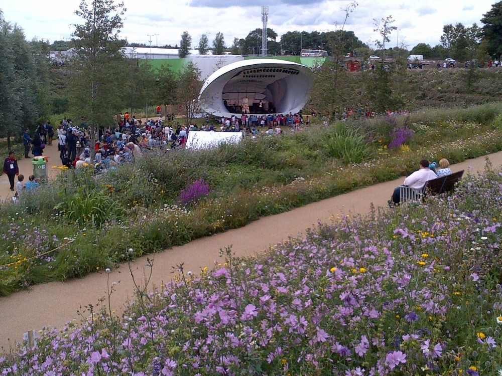 On a stage in the wildflower-filled Olympic park, that's Wenlock the mascot entertaining kids.