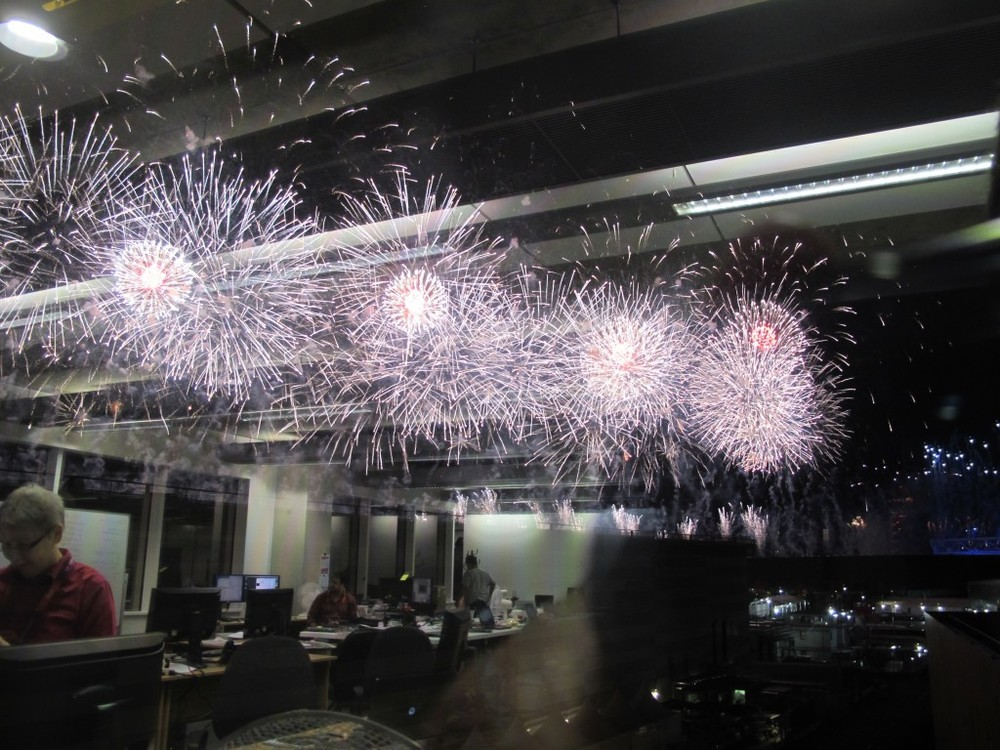 I took this photo of opening ceremony fireworks from our office in the main press center. I liked the reflection of our team (we have more than 50 staffers here) at work.