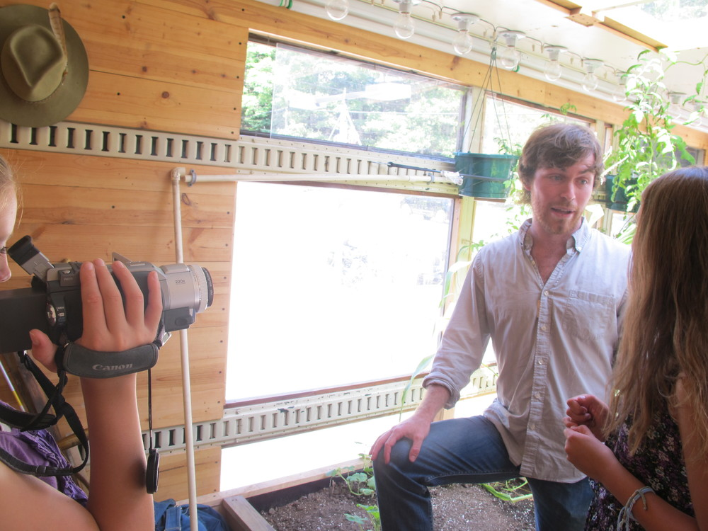 Lily the 12-year-old camerawoman and Anthea the 14-year-old reporter ventured inside the mobile greenhouse to interview Compass Green co-founder Nick Runkle for our Earth News kid-reporter program.