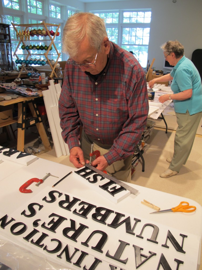 My dad and mom preparing signs and hat displays in The Naturalist's Notebook workshop at our house.