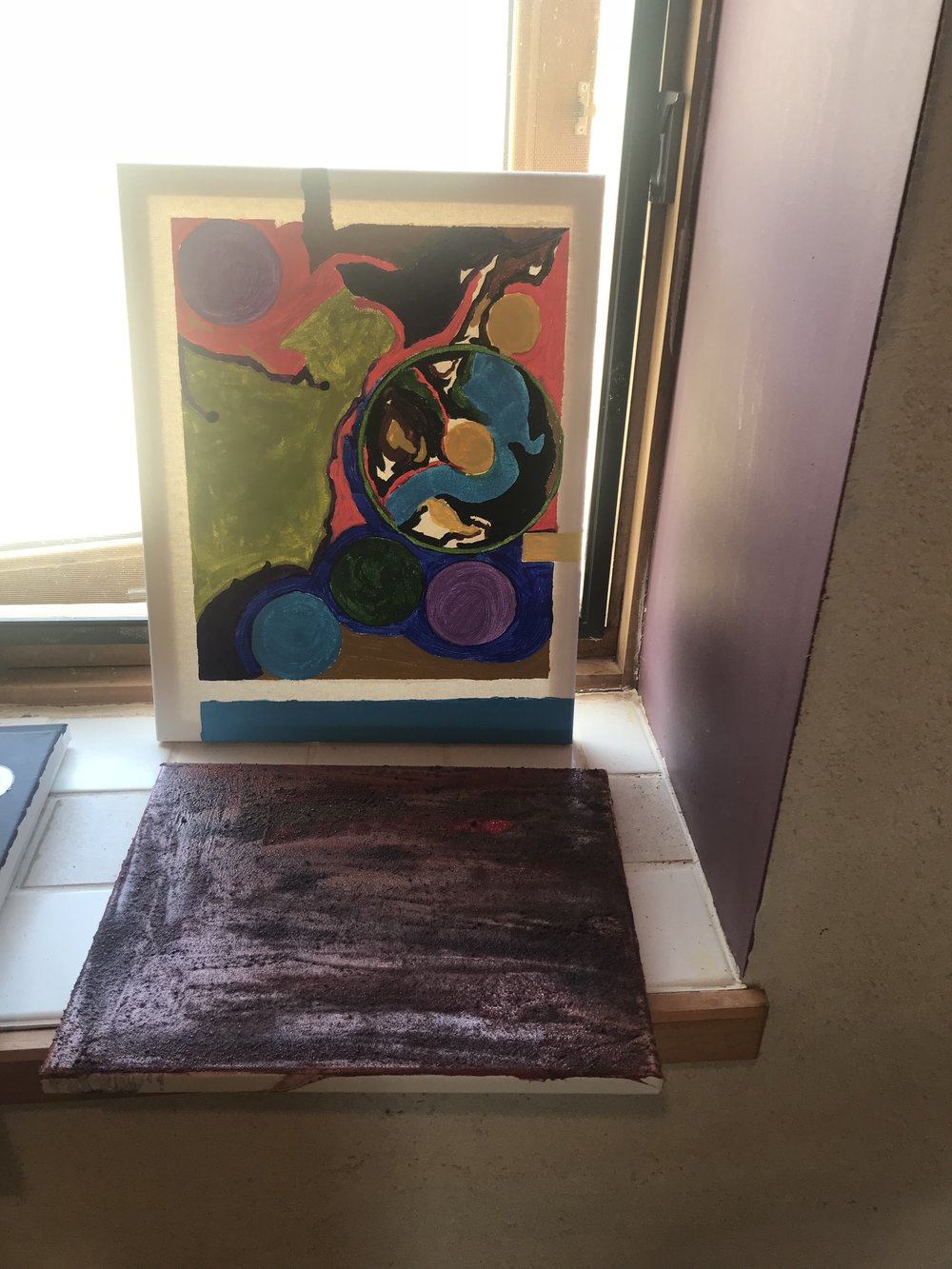 Two paintings, 'Rattlesnake' (standing) and 'Ant Hill' (laying flat) drying in the writer's studio, Wyoming, August 4, 2028
