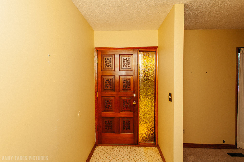 A photograph of a front door way with a wooden door in a very yellow home. There is harsh flash and high contrast.