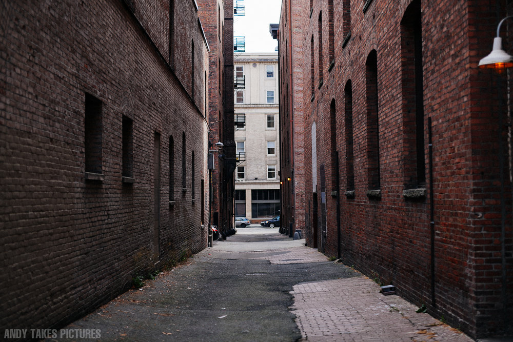A photograph of an old alleyway with brick buildings on either side. There is nothing in the alley except a red light. At the end is a sandstone building in the centre of the image.