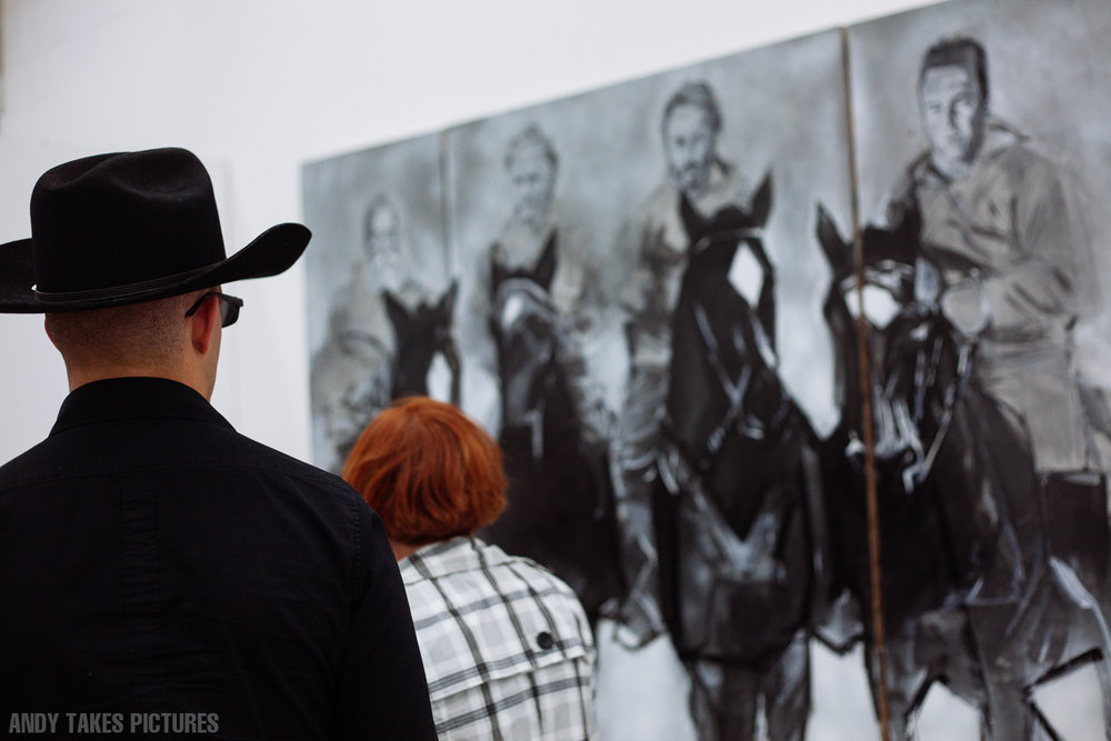 A photograph of a man with a black cowboy hat on the left of the frame is looking at a triptych of charcoal pictures on the right of the frame. The subjects of the triptychs are four cowboys riding horses.