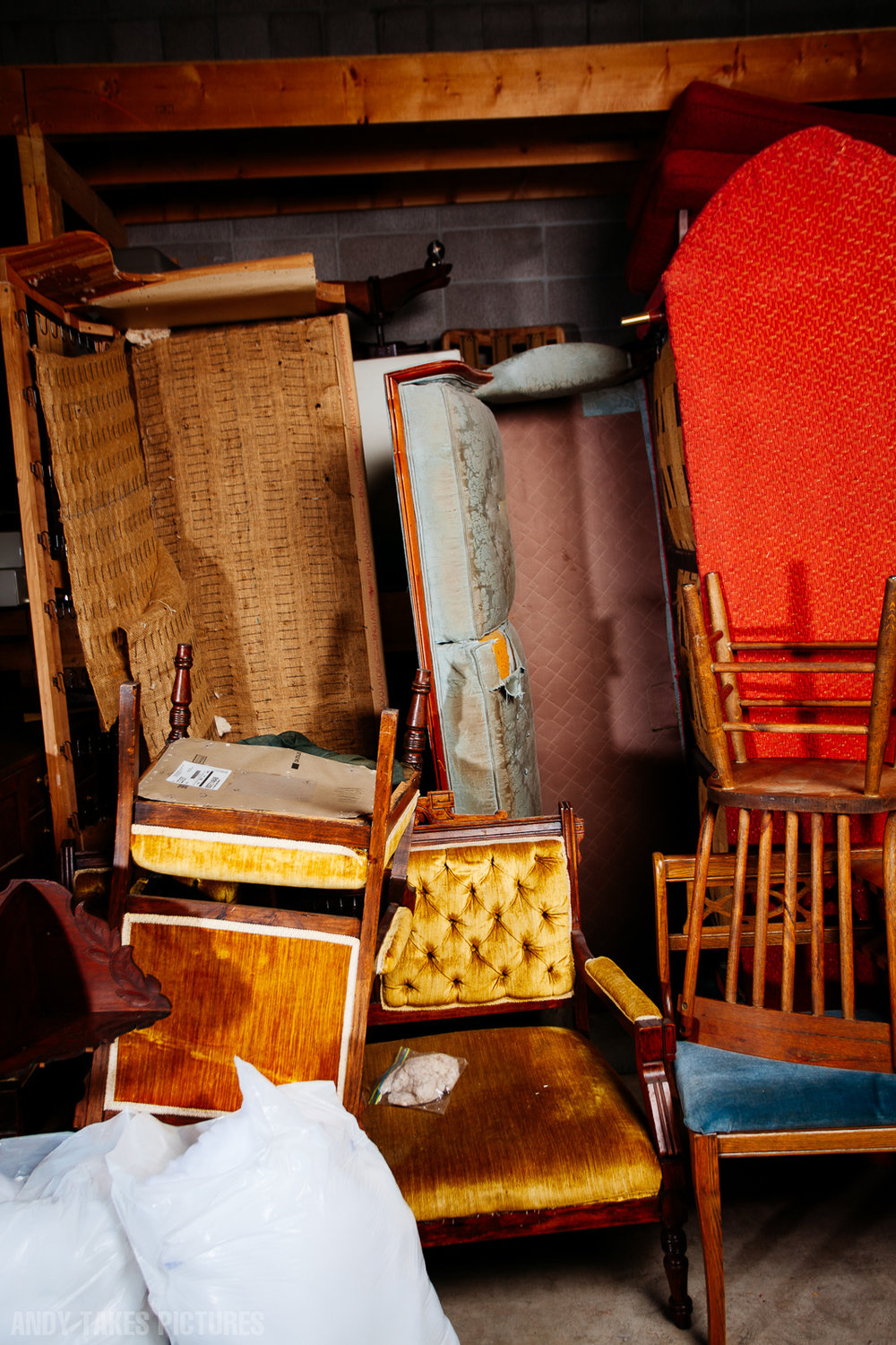A photograph of a pile of unupholstered couches and chairs. The couches are standing vertical and the chairs and strewn in front.