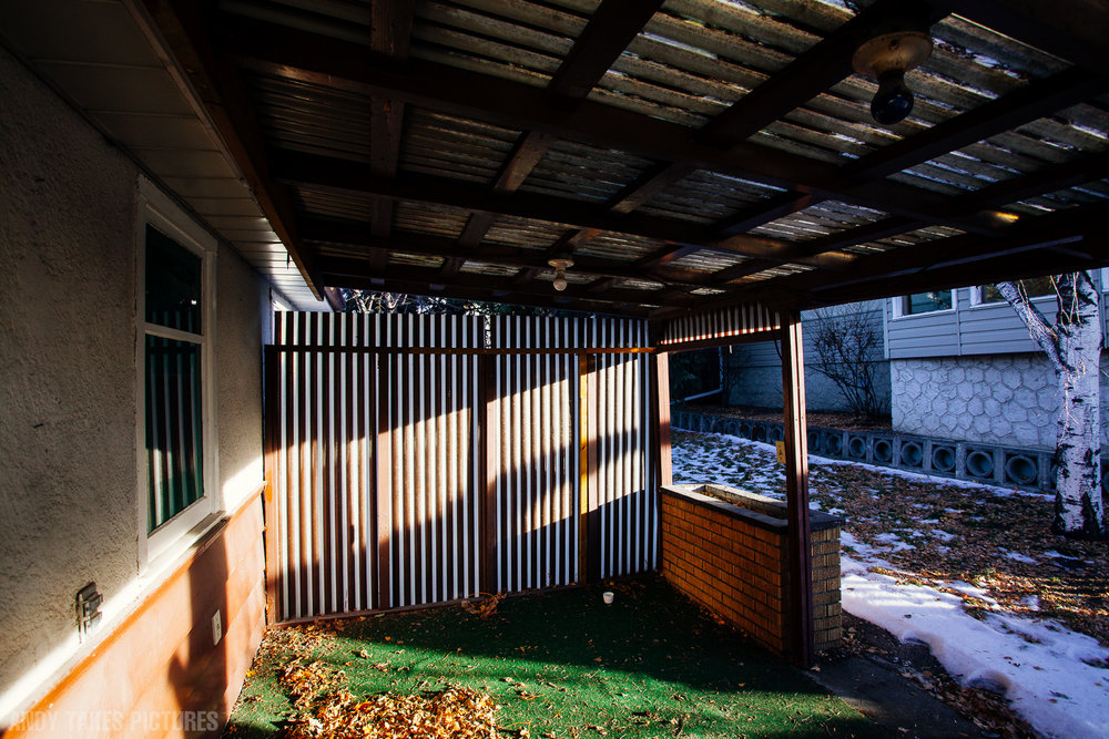 A photograph of a patio like space with faded astro turf and brick. The roof and wall are acrylic and the right side of the frame has a yard with some snow in it. The sun is low in the sky and streaming through the area.