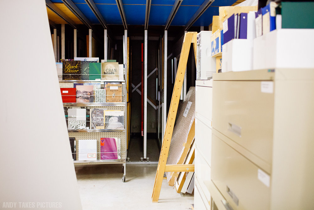 A photograph of a art storage room with some books. There is some blue and white acrylic around.