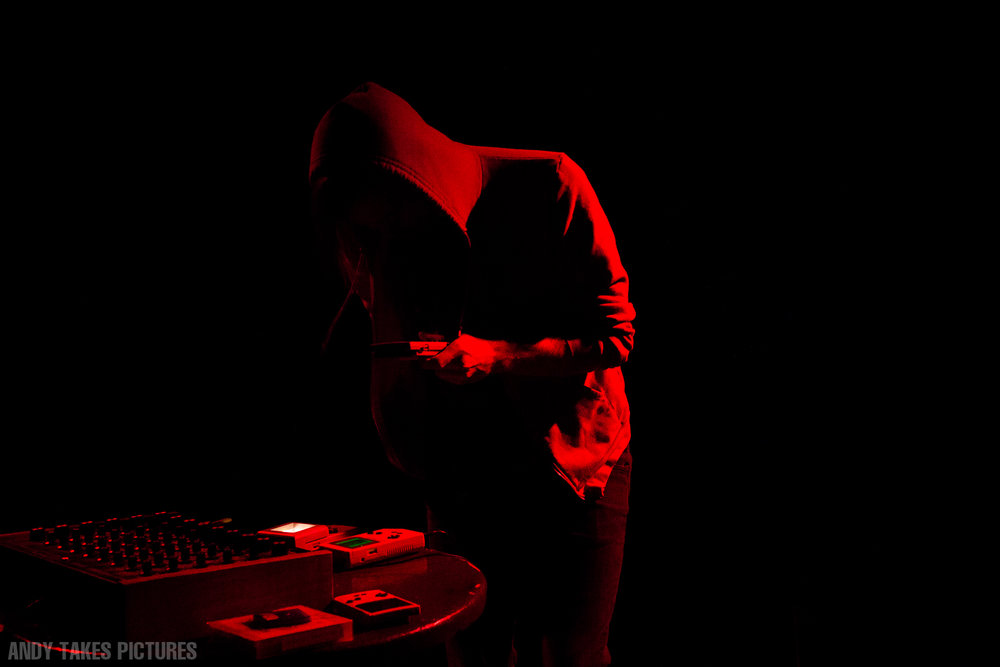 A photograph of local Calgary musician Grey Screen performing at a show. He is performing chiptune music on a series of Nintendo Gameboys that are the table in front of him. The photo is starkly lit and bright red.