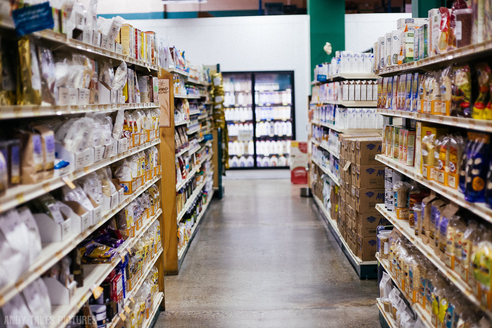 A photograph of community health foods in downtown Calgary. The aisle is empty. There are various products on either side.