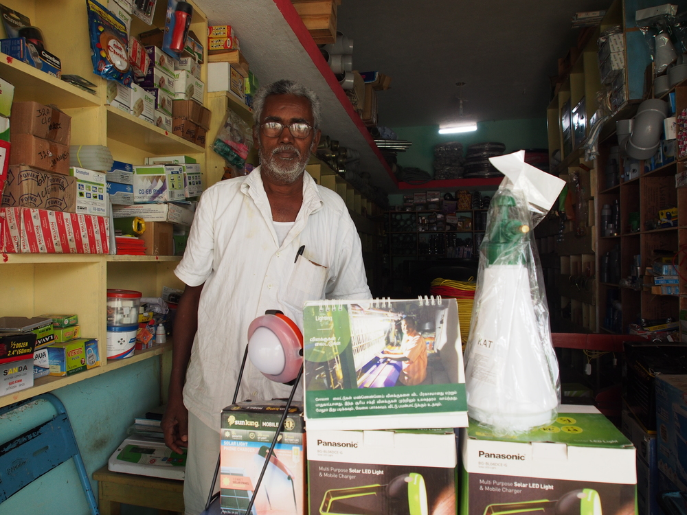 A shopkeeper displays  some popular Essmart products including an agricultural sprayer and solar lights