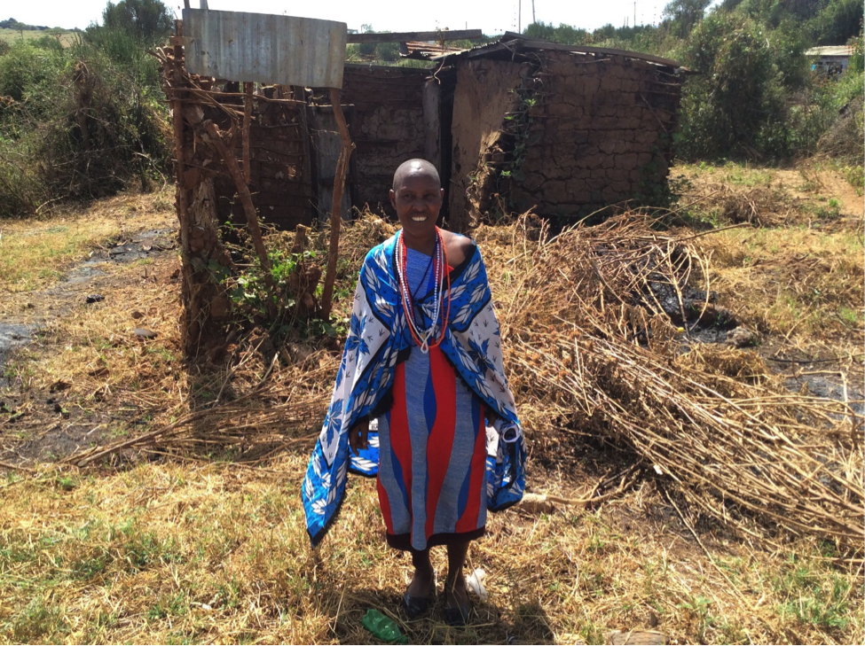 Maitei standing in front of her prior home.