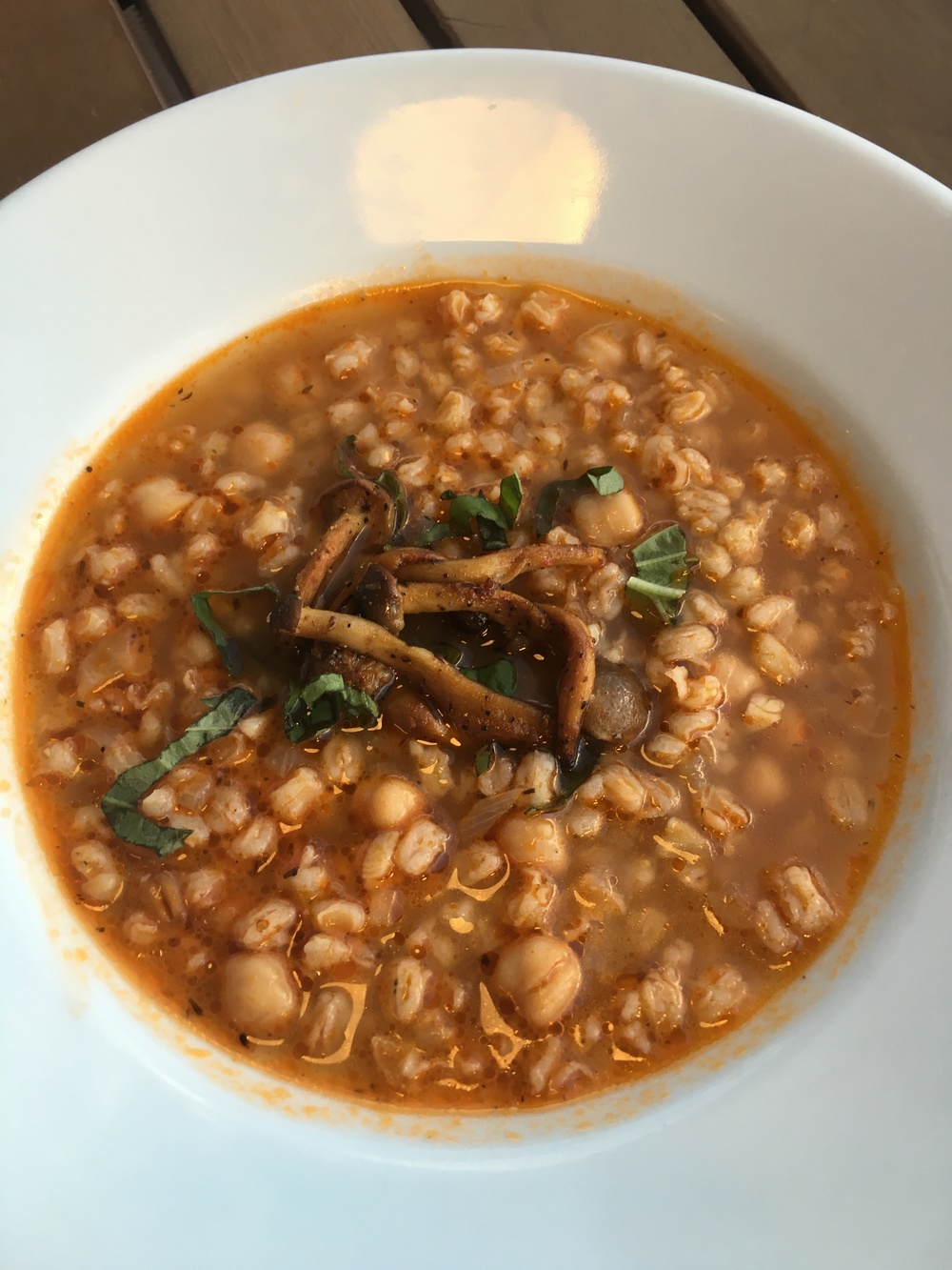 Dinner Appetizer Two: Chickpea farro soup topped with smoked mushrooms and basil.