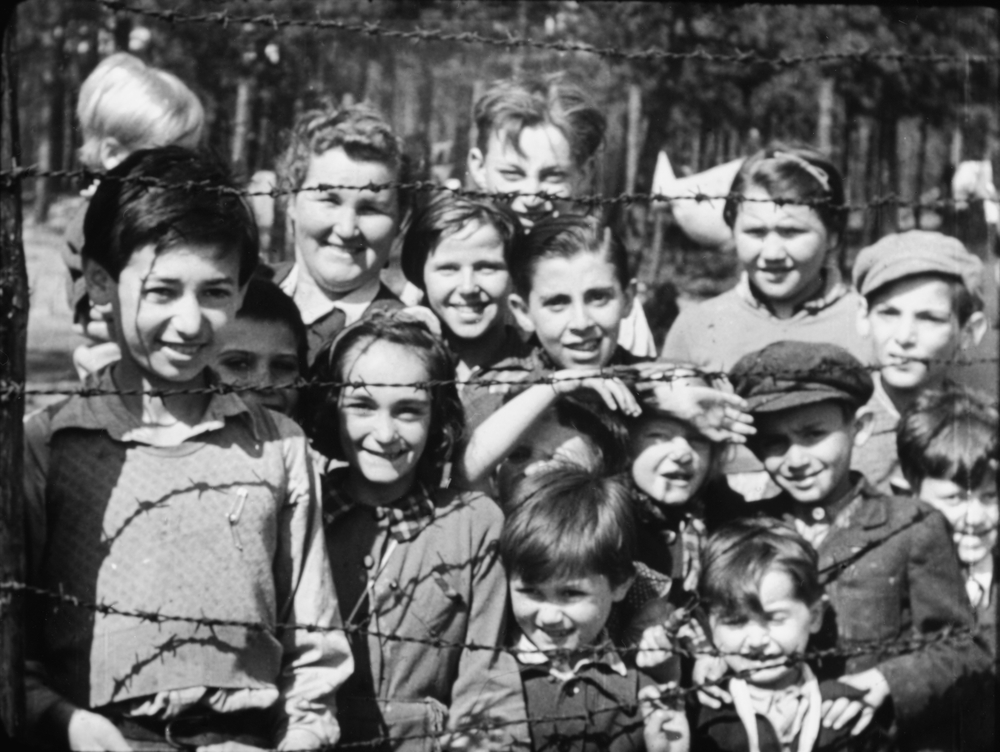 'Smiling children through barbed wire' taken by Sgt Lewis, 19-20 April 1945 IWM Film 1467.JPG