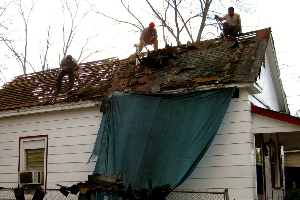 Our very first project in November of 2011 was a good-looking house in Fort Hill.  Ms. Ann's roof was almost rotten through in many places, causing water to damage the attic area and walls of the house. Blue tarps hung on two sides of the roof, covering places where rainwater ran into the house.  Professional roofers and volunteers scraped off four layers of roofing material before installing new decking and shingles. No more rain in Ms. Ann's house.