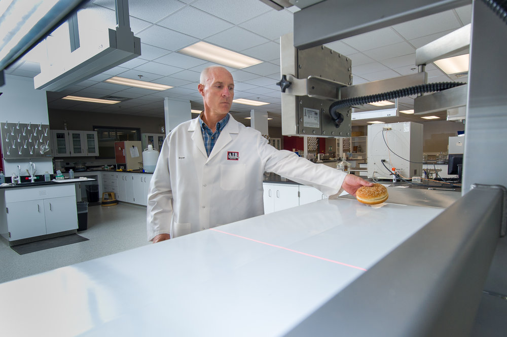 Glaser places a hamburger bun on the conveyor belt of the product imaging system.