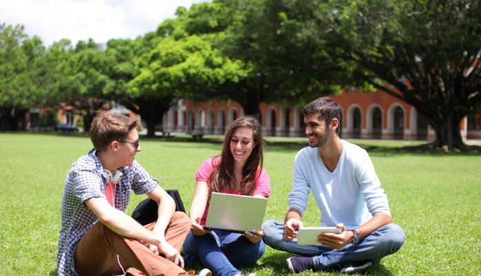 Students sitting on the grass with a computer