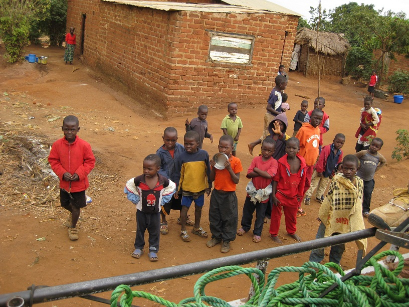 Crowd of kids watching the muzungu help offload bricks