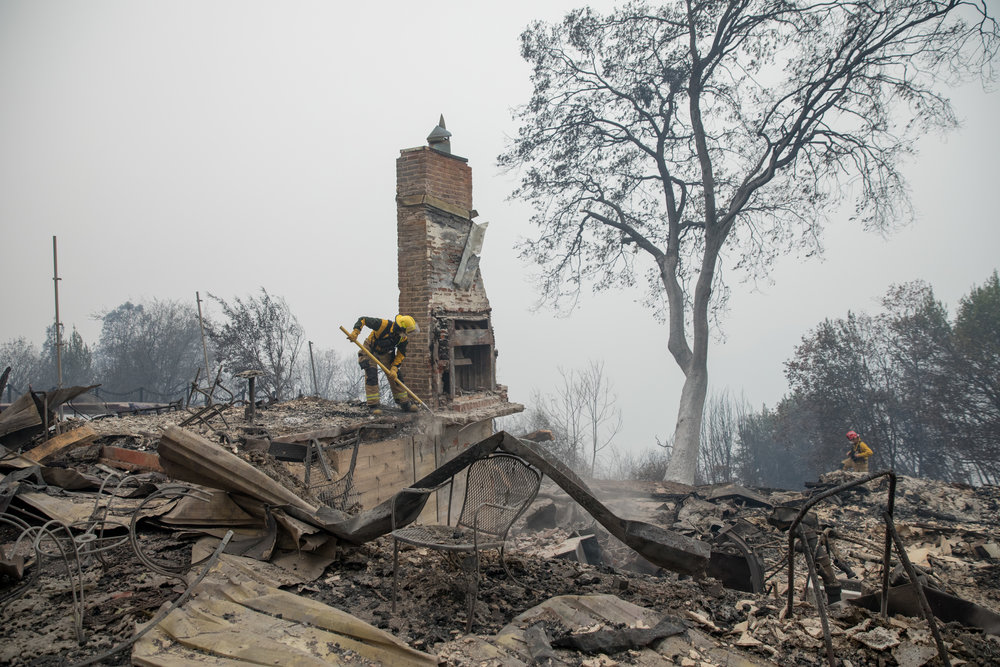 Firefighters from CAL FIRE clear away debris and try to knock out a chimney left standing before rescuers enter the scene in Paradise, CA — November 12th, 2018